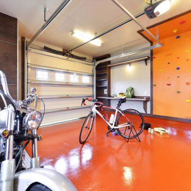 ガレージにあるボルタリング壁は、床の色に合わせたオレンジ色でポップなイメージに