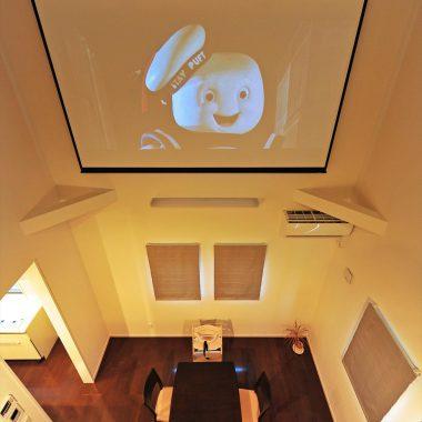 リビング吹き抜けにシアタースクリーン。リビングからも、二階からも観ることができる。2階での鑑賞は特等席♪