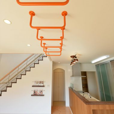 リビングにある雲梯で、やんちゃなお子様達も雨の日だって楽しめる。オレンジ色でお部屋のアクセントにも。