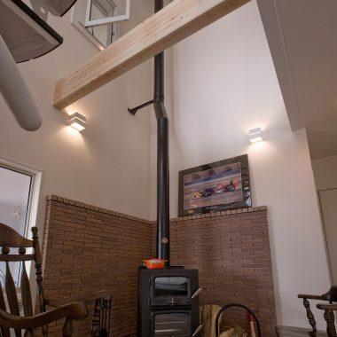 薪ストーブ廻りにはレンガ調ブロックで壁を仕上げ、床は灰が落ちても大丈夫なコンクリート下地のタイル貼り。お気に入りのインテリアで薪ストーブライフを楽しみます。