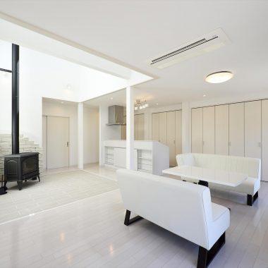 白を基調にしたリビング空間にシンプルな薪ストーブが際立ちます。